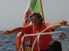Eugenio weating sunglasses, at the helm of his sailing boat